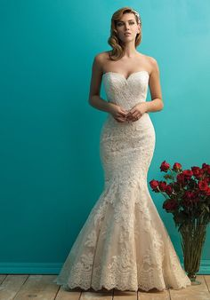 This simple, classic gown is designed to highlight the delicate lace covering the bodice and trailing down the skirt.