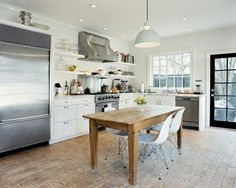 Great use of mixing modern chairs with farm table, stainless appliances with shaker style cabinets....it works.