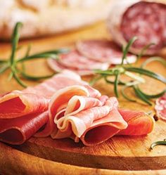 meat fondue recipes italian ham and salami with herbs. slices of prosciutto and salami. Italian Ham, Plateau Charcuterie, Specialty Meats, Prosciutto Crudo, Best Italian Recipes, Spicy Sauce, Food Backgrounds, Recipe Details, Yummy Appetizers