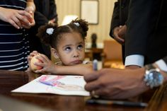 Luz Graham-Urquilla, 4, watches President Barack Obama as he signs her drawing at the Resolute Desk in the Oval Office, May 25, 2012. (Official White House Photo by Pete Souza)