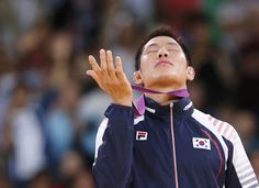 Gold medalist Kim Jae-Bum of South Korea...praying with his medal.