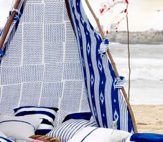 A tent on the beach, made of SOMNAR ($5.99/yd.) fabric with lots of white/blue cushions inside.
