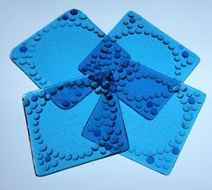Coasters, see through handcrafter and fired - set of four with non stick bubbles on bottom.