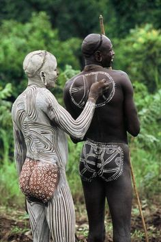Surma tribesmen, Omo Valley, Ethiopia. by Hans Silvester. *During the courtship season, Surma men spend hours perfecting their appearance. They create their principal body decoration by smearing the skin with a mixture of chalk and water and drawing intricate designs with their wet fingertips to expose the skin underneath (Monika Ettlin).