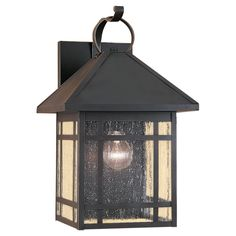 This Largo one-light outdoor wall fixture creates a warm and inviting welcome for your home's exterior. Inspired by the arts and crafts movement, Largo is a rustic, organic and charming fixture with an antique bronze finish and clear seeded glass.