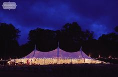 Twilight photo of this three pole sailcloth tent for a rustic and elegant backyard wedding in Stowe, VT.