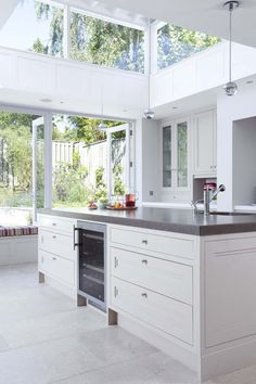 This open plan kitchen design features a wealth of natural light with a comfortable window seat and skylight. A stunning living space for the whole family.