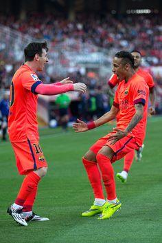 Lionel Messi (L) of FC Barcelona celebrates scoring their opening goal with teammate Neymar Jr. (R)during the La Liga match between Sevilla FC and FC Barcelona at Estadio Ramon Sanchez Pizjuan on April 11, 2015 in Seville, Spain.