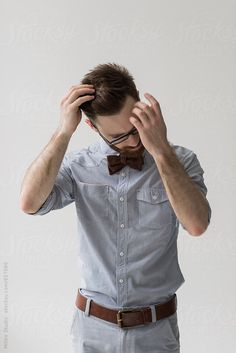 Close up of young bearded man adjusting hairstyle at home against white wall