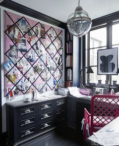 A pendant light fixture by Restoration Hardware, a vintage lacquer chair, and custom-made cabinetry in Megan's office.   - ELLEDecor.com