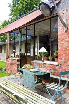 Terrasse en bois et façade en brique et verriere