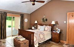 Master bedroom with tile floor, vaulted ceiling, brown walls, patterned comforter.