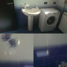 Il bagno allo stato attuale si presenta con lavabo a colonna e lavatrice - piastrelle sfumate sui toni del blu e bianco - decoro con fiori stilizzati