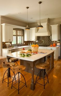 The charming brown-and-white kitchen was updated with a new island, including pendants and stools by Arteriors.