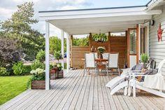 drewniany zadaszony taras ze skrzynkami z kwiatami, białymi leżakami i letnia jadalnią z kutym żyrandolem