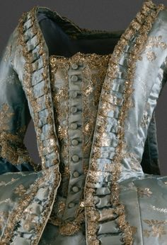 Interesting gown. Looks to be from the 1760s-1770s based on the silhouette and sleeve length, but I'm not sure I've seen a button-up stomacher for a gown from that period.