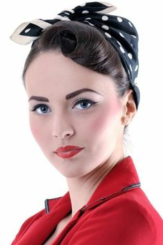 dark haired woman wearing black bandanna with white polka dots, eyeliner mascara and blush, penciled eyebrows and red lipstick, red blazer with black details