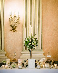 This candy table was filled with sweets in the celebration's color palette of white, gold, blush, and light peach. Lindt Champagne truffles, caramel marshmallows, macarons, and pink heart-shaped marshmallows were set out with flowers.