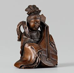 A Hida school okimono-type netsuke of Benten, by Shôko. Late 19th century     Seated in long flowing robes and with a billowing shawl, she holds a biwa in front of her. Signed Shôko.   Height 4.8 cm