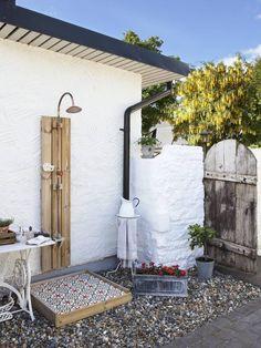 UTEDUSJ: En helt enkel utedusj blir en dekorasjon i hagen med enkle midler. Har du varmtvann blir det i tillegg behagelig. Her har eierne snekret en bakplate til å feste dusjen i, og laget en platting til å stå komfortabelt på, med betongfliser. Denne er greit å legge løs, ettersom betongfliser vil sprekke om de ligger ute om vinteren. Planter i potter og et lite bord til såpene gjør hjørnet komplett.