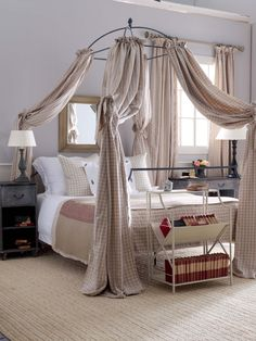 A wrought iron canopy bed with gingham hangings creates a cool country look. Iron Canopy Bed, Neutral Bedrooms, Light Of Life, Neutral Colour Palette, Cool Countries, Wrought Iron, Gingham, Curtains, Country