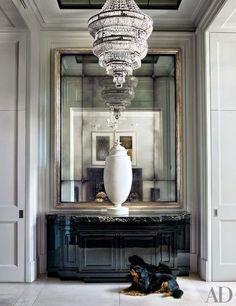 architectural digest foyer vignette crystal chandelier oversized gold gilt mirror