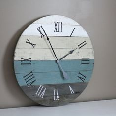 Welcome to the one and only terrafirma79 designs. Thank you for considering our artisan pallet wood clock shop for your home decor or gift giving needs.  Here is a LARGE ~26 round pallet wood clock. Its circle shape is perfectly imperfect, which, of course, adds to the eclectic, rustic, beachy look for your home. We hope you love the blend of beach-inspired colors in neutrals and teal with a hint of blue. This modern yet rustic reclaimed wall clock is perfect for your rustic, beach or…