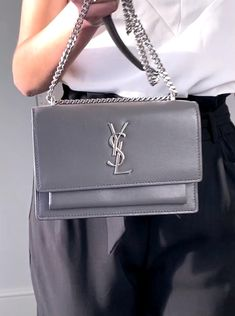 Are you looking for a designer bag that constantly looks great and can go from day to evening effortlessly? Then look no further than the Saint Laurent Sunset Bag. In this blog and video we review the bag including pricing and where to buy. Featured in this video is the Mini / wallet on chain YSl sunset bag in grey and silver. #YSLBag #SaintLaurentBag #YSLSunset #YSLSunsetbag #SaintLaurentSunsetbag #SaintLaurent #DesignerBag #EveningBag #DesignerEveningBag Saint Laurent Handbags, Saint Laurent Bag, Ysl Sunset Bag, Ysl Bag, Celebrate Life, Luxury Bags, Evening Bags, Purses And Handbags, Fashion Bags