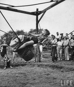 Woman attempting to ride a bucking barrel that rides like a horse on Mayan Dude Ranch, Texas. September 1953.