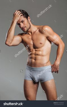 Attractive brutal man in underwear posing isolated on a gray background