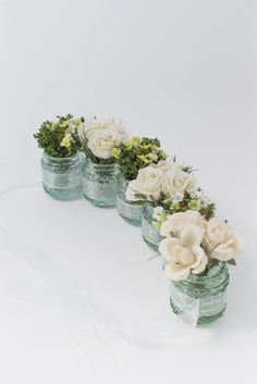 Vintage Vases Collection Tied with Ribbon. Paper Whites stunningly realistic artificial floral arrangements are designed and hand made in the UK. Produced to depict a fresh start and evoke memories to lift the spirits. All arrangements come with the beautiful vases you see in the picture. This vintage vase collection makes a beautiful centrepiece. Six mini glass jars linked together with organza ribbon filled with dried and artificial roses. Height - 8.5cm
