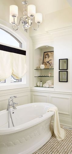Master ensuite with built in display niche, classical panel moulding and sculptural free-standing bath tub. Regina Sturrock Design Inc