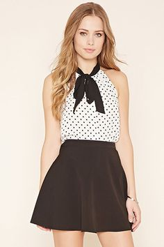 A sleeveless semi-sheer top featuring a polka dot print, contrast self-tie neck, and buttoned front.