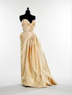 "1949 ""Gruau"" House of Dior silk gown. In addition to the full bouffant skirts he debuted in the ""Corolle"" collection of 1947, Christian Dior also often worked with an asymmetrical design aesthetic, particularly in the 1948-1949 collections. This gown from 1949 is characteristic of this style, in which the gown appears to be twisted around the body. Voa MMA."