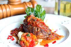 A classic Italian dish of super tender veal shank braised together with vegetables, herbs, wine and broth, served with mashed potato and tomato sauce