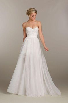 Come see wedding dresses we're loving, including this classic belted strapless ballgown style