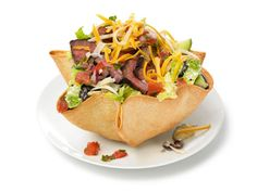 Inspired by Moe's: Almost-Famous Steak Taco Salad    At the popular chain Moe's, the taco bowl alone has 390 calories and 26 grams of fat. But if you're addicted to Moe's Close Talker salad, don't despair: Chefs in Food Network Kitchens created this copycat with a slimmed-down shell that's baked instead of fried.