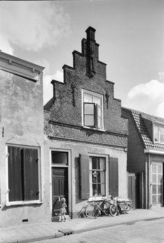 Achterstraat 69 in Vianen. Pand met trapgevel waarin geprofileerde waterlijsten, ontlastingsboog, sierankers en toppilaster op gebeeldhouwde kop in Vianen.