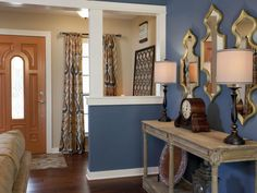 ENTRY/LIVING ROOM, AFTER: The Property Brothers removed the wood paneling and added color, bringing in new mirrors and accessories combined with an old clock that's been in the couple's family for generations.