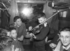 A Jewish refugee boy leaving Germany on a train in 1938, playing the violin. Photo: The Wiener Library (Ref: WL31).