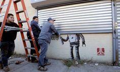 Banksy : The Coney Island stencil hidden with  a rolling shutter door.