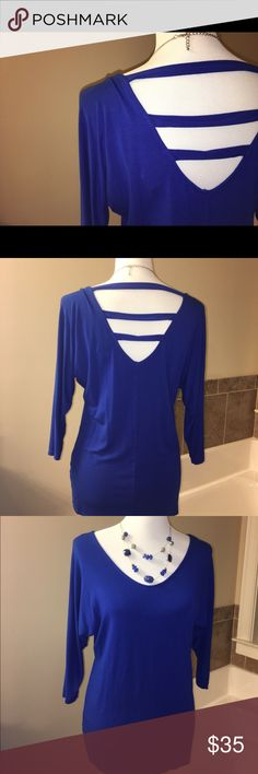 White House Black Market tunic Hide your arm fat in this sexy royal blue tunic.  Unique cut outs on back and v-neck in front.  Elbow length sleeves and soft jersey knit.  Perfect with black legging capris for summer nights. White House Black Market Tops Tunics