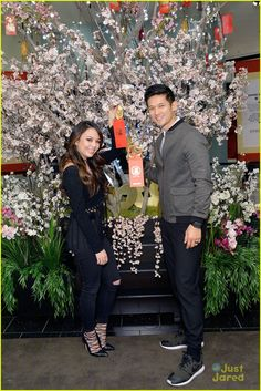 Janel Parrish and Harry Shum Jr. hang their wishes on the wishing tree during the 2016 Lunar New Year Celebration event