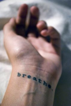 Modern serif font. Breathe tattoo, on wrist.