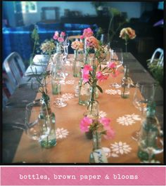 Brown paper tablecloth made fun with stenciled flowers and upcycled bottle vases. Simple and charming