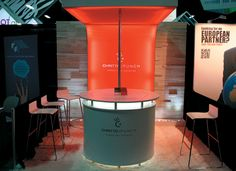 """""""almost theatrical effect. A circular, internally lit reception desk anchors the exhibit and draws the eye toward the glowing red structure at the back"""" #exhibit #design #tradeshow"""