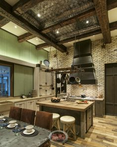 A rustic country kitchen mixed with industrial design for a thoroughly unique room. The stone and wood of the cooking area and distressed ivory cabinets are mixed with an industrial dining table and shutters. Accents in the kitchen are copper and vintage flea market finds like an old scale. The ceiling is a mixture of exposed wood beams and an ornate metal section.