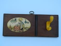 Vintage Holly Hobbie replica shelf with yellow coat hook includes placque with the cute bonnet girl and her cat in the kitchen. $23.00, via Etsy.