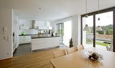 Offene Küche modern weiß mit Kücheninsel und Esstisch Holz - Inneneinrichtung Baumeister Haus Leitner - HausbauDirekt.de