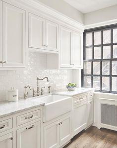 White butlers pantry boasts white glazed brick backsplash tiles between shaker cabinets and satin nickel knobs.